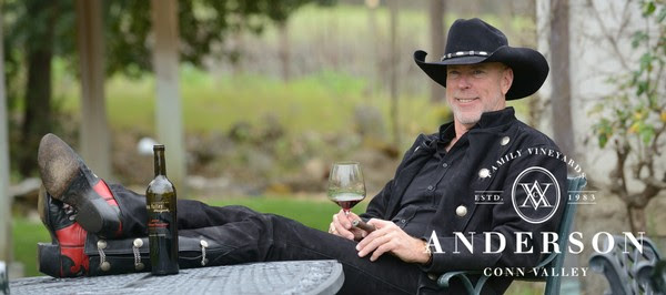 man in black cowboy clothes enjoying a glass of wine on outdoor table